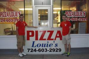ethan and nick with shop sign